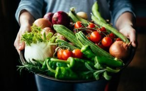 person holding silver bowl with variety of raw vegetables